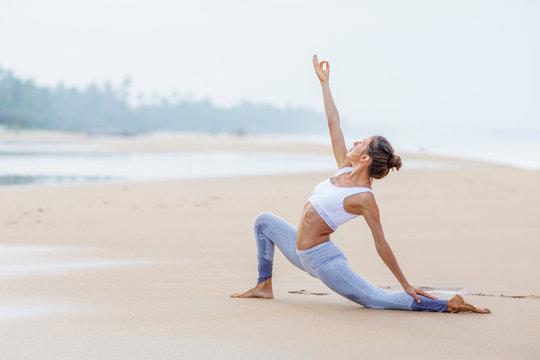 Caucasian woman practicing yoga at seashore of tropic ocean