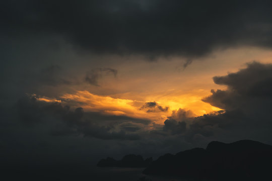 dark dramatic sky during golden yellow sunset on exotic island, thailand