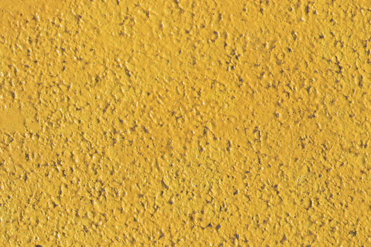 Yellow painted asphalt texture. Colored road surface background.