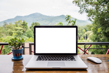 blank screen of laptop with mouse and  plant vase on wooden table, Mountain and forest background