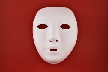 Plastic white face mask stock images. White mask on a red background. Plastic human mask