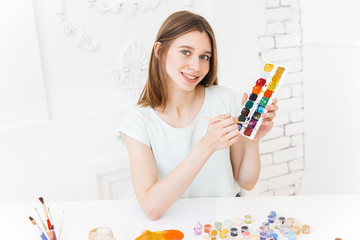 Pretty smiling young woman drawing a picture