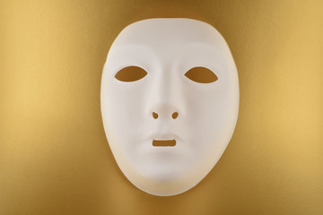 Plastic white face mask stock images. White mask on a gold background. Plastic human mask
