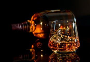 Whiskey with ice in glass and a bottle of whiskey on black background