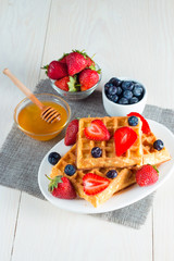 Photo of fresh homemade food made of berry Belgian waffles with honey, chocolate, strawberry, blueberry, maple syrup and cream. Healthy dessert breakfast concept with juice.