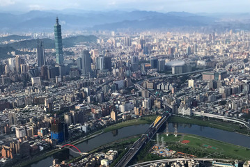 Nan Shan Plaza and Taiwan's landmark building Taipei 101 are pictured through the window of an airplane, in Taipei