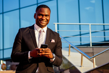 handsome and stylish afro american business man in a fashionable black jacket and a white shirt with a collar holds a smartphone in hand background of Manhattan glass offices cityscape