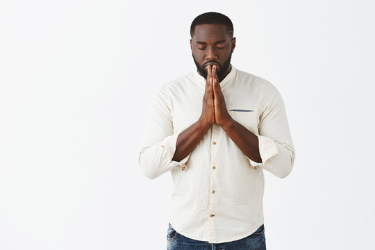 Indoor shot of focused and determined very serious African American man in white shirt, closing eyes, holding hands in pray and making wish, praying or hoping for better over gray background