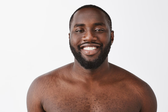 Beauty, people and emotions concept. Waist-up shot of happy handsome African American standing naked over gray background, smiling with satisfied and confident smile at camera