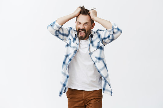 You make me man. Portrait of stressed intense and bothered crazy bearded man, pulling hair out of head and screaming from anger and negative emotions, yelling, being pissed and fed up of everything