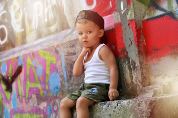 A two-year-old baby boy in a hip hop style clothes is sitting alone under the wall with graffiti and very upset