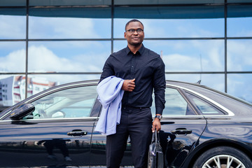 successful businessman handsome African American man in a stylish suit in a blue jacket black shirt and glasses standing in front of a cool new black car on the street