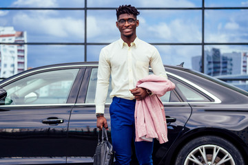 successful businessman handsome African American dreadlocks man in a stylish suit in pink jacket and glasses standing in front of a cool new black car on the street