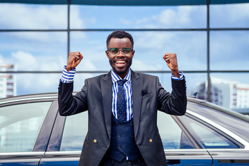 happy lucky and successful afro american businessman rejoices and enjoying success ahead of the car. concept of a good deal and victory