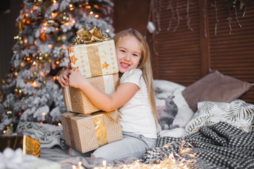 Cute little child holding christmas presents