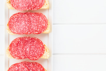 Salami slices on ciabatta bread, photographed overhead on white wood (Selective Focus, Focus on the salami slices)