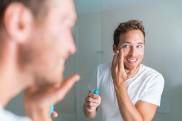Smiling young man putting face cream under eyes to treat wrinkles or undereye eyebags, Anti-aging facial treatment. Male beauty.