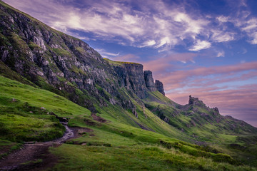 View on Quiraing hiking trail along the high cliffs during early sunset with pink clouds on blue sky, Isle of Skye, Scotland