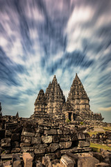 Magnificent Prambanan Hindu Temple from north park view with dramatic motion blur cloudy blue sky background