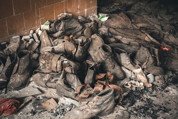 Pill of old shoes on a dusty floor in a war-torn house, ruined dark building inside interior, aftermath of disasters concept