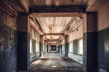 Dirty empty dark corridor in abandoned building, perspective