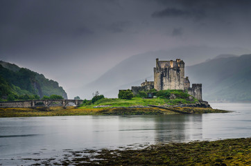 Scottish medieval Eilean Donan castle peaking from a lake during cloudy weather