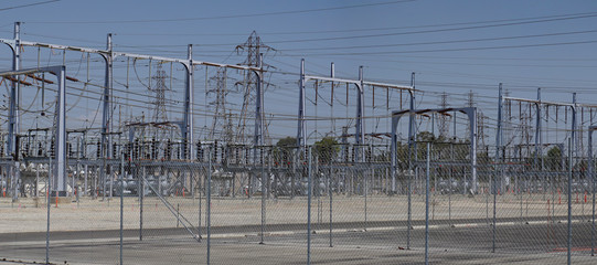 Electric power transmission substation with a large network of interconnected lines, transformers, wires, cables, insulators and towers feeds the electrical grid.