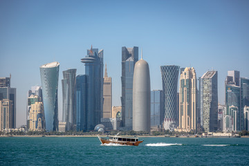 The skyline of Doha with a traditional boat in the foreground in Qatar, on a blue sky day, winter time, seen from the MIA Park