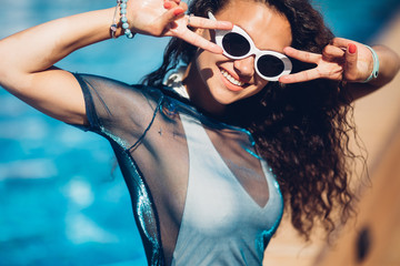 Close-up portrait of magnificent caucasian girl in round white sunglasses. Lovable long-haired brunette woman enjoying life and having fun at resort.