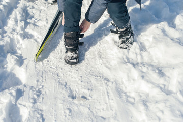 Boy teenager on skis in a park of winter snow drifts