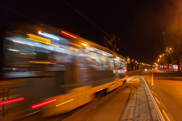 The motion of a blurred tram down the street in the evening.