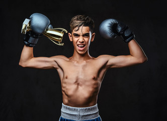 Joyful young shirtless boxer champion wearing gloves holds a winner's cup. Isolated on the dark background.