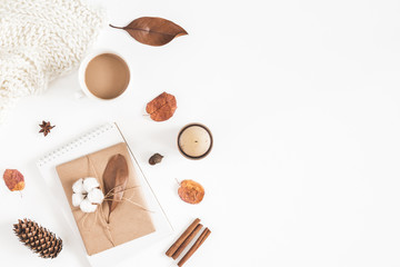 Autumn or winter composition. Cup of coffee, gift, dried autumn leaves, beige sweater on white background. Flat lay, top view, copy space