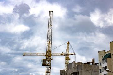 Construction crane against a cloudy sky background