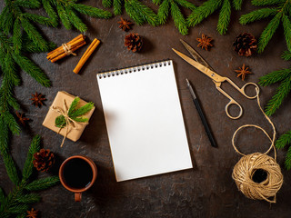 Empty white notebook and pen on dark black Christmas background of fir branches, cones, gifts. Letter, mock up