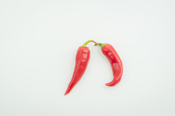 Two chili peppers on a light background
