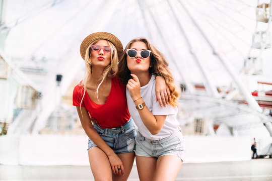 Best friend having fun near Ferris wheel, going crazy together, wearing hats and mirrored sunglasses, amazing view on the city, bright colors evening sunlight