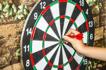 A man plays darts and holds the dart with his hand to hit the target on the target.