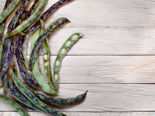 Fresh raw uncooked beans in the pods and open pods of beans with fruits lie on a wooden background