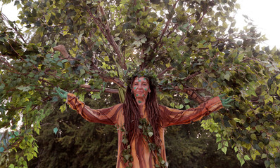 A woman poses as a tree during the Zuercher Theater Spektakel theatre festival in Zurich