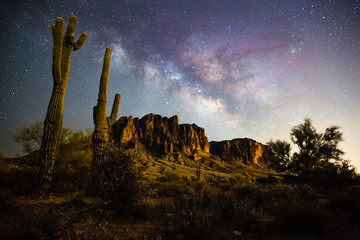 Tuinposter Aubergine A starry night time desert landscape with the milkyway. Milkyway rising behind the superstition mountains. Arizona