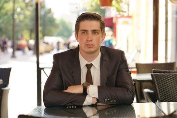 young man in black business suit, white shirt and tie
