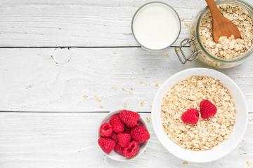 Ingredients for healthy breakfast - miilk, raspberries and oat muesli on white wooden table. top view