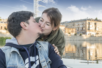 Woman standing behind man kissing him on the lips on the city background with reflection in water