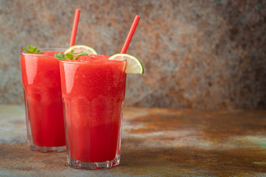 Watermelon slushie with lime, summer refreshing drink in tall glasses on a blue rusty background. with copy space