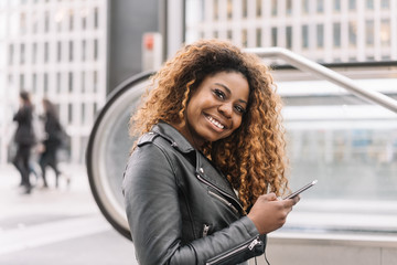 Young smiling black woman holding mobile phone
