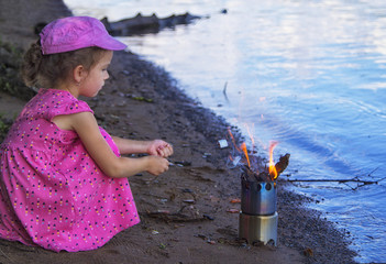 a cute little girl  in pink dress cooking a marshmallow with a camp stove by the river