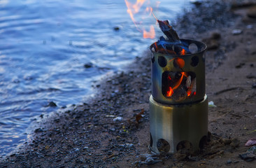Camping Stove at the edge of the river. Outdoor equipment