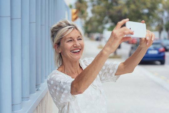 Cheerful mature woman talking selfie on smartphone