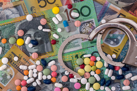 Opened handcuffs with dispersed pills on australian dollar background